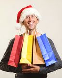Christmas man. Man holding shopping bags. Christmas sales. Man wearing Santa claus hat in shopping time. New year holidays. Christ. Mas gifts. Excited man in stock images