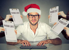 Christmas man in santa hat receiving gift requests buying online Royalty Free Stock Image