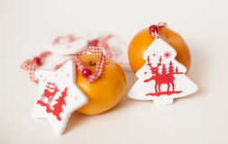 Christmas mandarins. Tangerines with Christmas toys on a white background Royalty Free Stock Photos