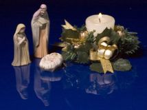 Christmas Manger. Figurines with candle and greenery Stock Image