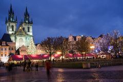 Christmas market. Sunset on Old Town Square with St. Teyn gothic cathedral in Prague during Christmas market with walking people Royalty Free Stock Photo