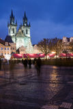 Christmas market. Sunset on Old Town Square with St. Teyn gothic cathedral in Prague during Christmas market with walking people Royalty Free Stock Images