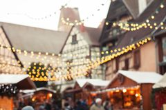 Christmas market blurred background, people walking in cozy decorated street stock image