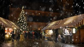 Christmas Market in Frankfurt, Germany. Christmas market spirit during snow night. Celebrating Xmas holidays. Lights, carousel, small houses at the market in the stock video