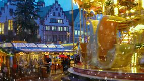 Christmas Market in Frankfurt, Germany. Christmas market spirit during snow night. Celebrating Xmas holidays. Lights, carousel, small houses at the market in the stock video footage