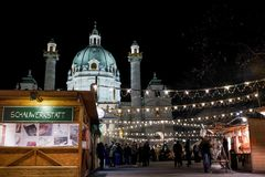 Christmas market at Karlsplatz with Karlskirche St. Charles` Church on the background. People eating, chatting and buying presents at christmas market at stock photo