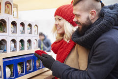 Christmas market with loving person. Big choice of colorful christmas balls Stock Photos