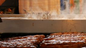 Christmas market, national German sausages are grilled, next to buns. Women`s hands turn Nuremberg sausages with help of. Christmas market, national German stock video footage