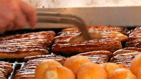 Christmas market, national German sausages are grilled, next to buns. Women`s hands turn Nuremberg sausages with help of. Christmas market, national German stock video