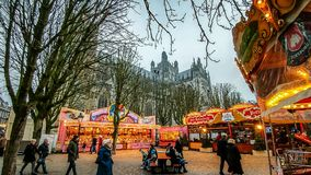 Christmas market in `s-Hertogenbosch, the Netherlands. A Christmas market at dusk with walking people, illuminated stalls, a merry-go-round and the cathedral St Stock Photo