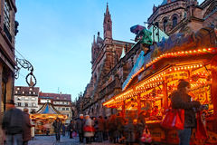 Christmas Market in Strasbourg. Strasbourg,France- December 12, 2012: Image of people walking among festive street stands and merry-go-round in Broglie Square Royalty Free Stock Photos