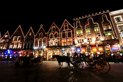 Christmas in Markt sqaure, bruges. Night picture at Christmas showing horse drawn carriages in Markt Square, Bruges, with typical illuminated Belgium Royalty Free Stock Images