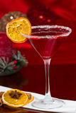 Christmas Martini. Served with dehydrated oranges and spices on a red holiday background Royalty Free Stock Photography