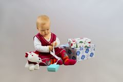 Baby Girl In Red Dress Sitting And Opening Gift Boxes. Stock Photos