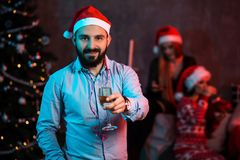 Christmas, x-mas, New year, winter, happiness concept - smiling man in santa helper hat with a glass of champagne Royalty Free Stock Photography