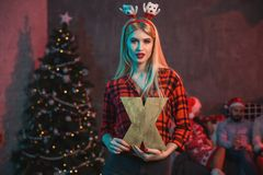 Christmas, x-mas, New year, winter, happiness concept - smiling woman in santa helper hat with a wooden letter X. Stock Photos