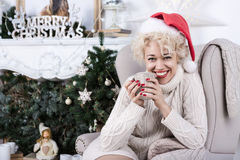 Christmas, x-mas, new year, winter holidays, happiness concept. Smiling woman in santa helper hat  in Christmas decorations Interior with knitted elements Royalty Free Stock Image