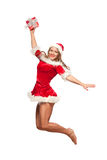 Christmas, x-mas, winter, concept - smiling woman in santa helper hat with gift box, happiness jump for joy isolated on Stock Photo