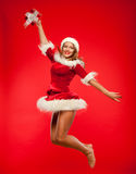 Christmas, x-mas, winter, concept - smiling woman in santa helper hat with gift box, happiness jump for joy over red Stock Photo