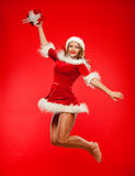 Christmas, x-mas, winter, concept - smiling woman in santa helper hat with gift box, happiness jump for joy over red Royalty Free Stock Photo