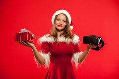 Christmas, x-mas, winter, happiness concept - Beautiful young brunette with long hair in santa helper hat wearing. Virtual reality headset over red background Stock Photo
