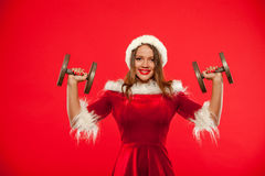 Christmas, x-mas, winter, happiness concept - Bodybuilding. Strong fit woman exercising with dumbbells in santa helper. Hat , over red background. Muscular Stock Images