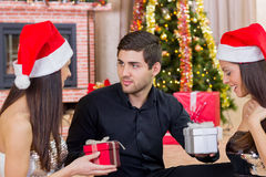Christmas, x-mas, winter, valentine's day, birthday, couple, hap. Man gives gifts twin sisters on Christmas night stock photo