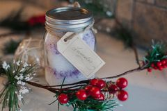 Christmas Mason Jar filled with Epsom Salt. Just in time for Christmas. A DIY Rustic mason jar filled with lavender epsom salt surrounded by holly berries and a Royalty Free Stock Photography