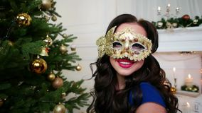 Christmas masquerade, beautiful girl in mask celebrating New Year, looks at the camera, sends a kiss, party near stock video footage