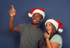 Surprised women man pointing up christmas red hat santa claus december holiday party young couple. Christmas men and women wearing santa claus red hat pointing Royalty Free Stock Photography
