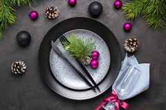 Christmas menu concept . Flat lay with Xmas decorations, dark plates, fork and knife with napkin. Christmas menu concept . Flat lay with Xmas decorations, dark stock photography