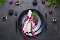 Christmas menu concept . Flat lay with Xmas decorations, dark plates, fork and knife with napkin. Christmas menu concept . Flat lay with Xmas decorations, dark stock photo
