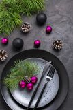 Christmas menu concept . Flat lay with Xmas decorations, dark plates, fork and knife set with napkin. Copy space royalty free stock image