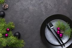 Christmas menu concept . Flat lay with Xmas decorations, dark plates, fork and knife set with napkin. Copy space stock image