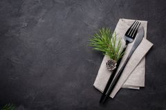 Christmas menu concept . Flat lay with Xmas decorations and pine cones, dark fork and knife set with napkin. Copy space stock photo