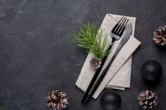 Christmas menu concept . Flat lay with Xmas decorations and pine cones, dark fork and knife set with napkin. Copy space stock photography