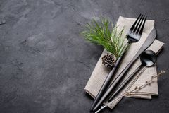Christmas menu concept . Flat lay with Xmas decorations and pine cones, dark fork and knife set with napkin. Copy space stock images
