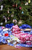 After Christmas Mess. A Mess of Wrinkled Wrapping Paper Scattered Under the Christmas Tree stock photos