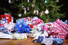 After Christmas Mess Landscape. A Mess of Wrinkled Wrapping Paper Scattered Under the Christmas Tree Royalty Free Stock Image
