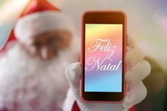 Christmas message in portuguese: Feliz Natal from Santa Claus or Saint Nicholas showing cell phone screen. Blurred background. With Father Christmas holding stock image