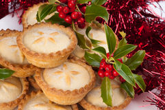 Christmas Mince Pies with Holly and Decorations. Christmas mince pies with holly and berries and christmas decorations royalty free stock images