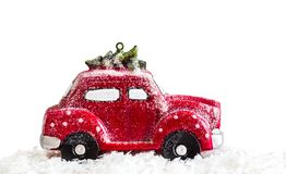 Christmas miniature car. Creative image of a red Christmas miniature car with a Christmas tree on a white background; Christmas holiday; New Year royalty free stock photography