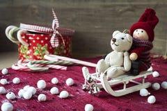 Christmas miniature toys on wooden backround. Sledges and gift b. Christmas decor - miniature toys on sledges. Gift box with candies on wooden background Royalty Free Stock Photos