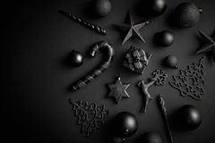 Christmas minimalistic and simple composition in mat black color. Christmas gifts, decorations on black background. Flat lay, top view with copy space stock image