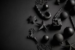 Christmas minimalistic and simple composition in mat black color. Christmas gifts, decorations on black background. Flat lay, top view with copy space royalty free stock images