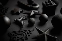 Christmas minimalistic and simple composition in mat black color. Christmas gifts, decorations on black background. Flat lay, top view stock photo