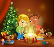 Christmas miracle - boys opening a magic gift beside a Christmas tree Royalty Free Stock Images