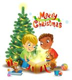 Christmas miracle - boys opening a magic gift beside a Christmas tree Royalty Free Stock Photography