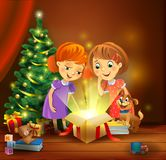 Christmas miracle - girls opening a magic gift beside a Christmas tree Royalty Free Stock Photos
