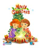 Christmas miracle - girls opening a magic gift beside a Christmas tree Royalty Free Stock Image